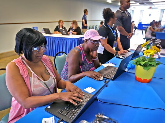 Romonda Carter, left, and and Keonya Burt join others as they fill out applications, at the Walmart job fair, Tuesday, May 15, 2018.  Walmart  is having a two-day job fair May 15 and 16 at the Indiana State Fairgrounds, in Grand Hall, from 10am-8pm.  They are hoping to fill jobs in the Plainfield store.
