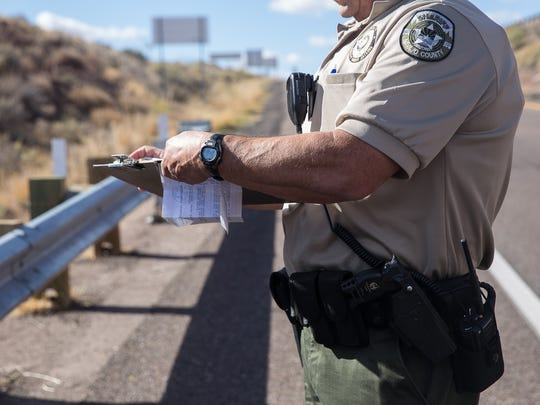 A Navajo County Sheriff's Office deputy fills out paperwork