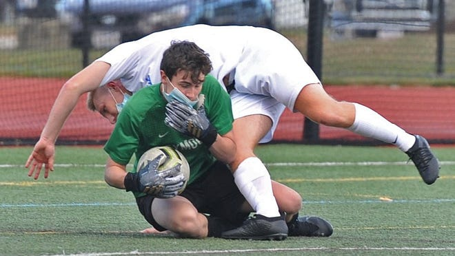 Weymouth goalie Aaron Cassidy makes a save as Braintree's Alex Toye tumbles over him during boys soccer at Weymouth High School, Tuesday, Oct. 6, 2020. Tom Gorman/For The Patriot Ledger