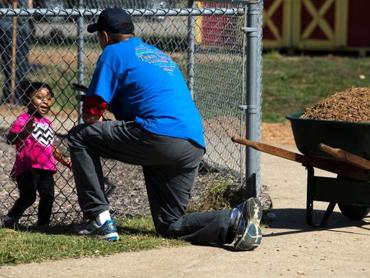 Ja'Mia Tapp, 2, visits with volunteer Brad Ellsworth,