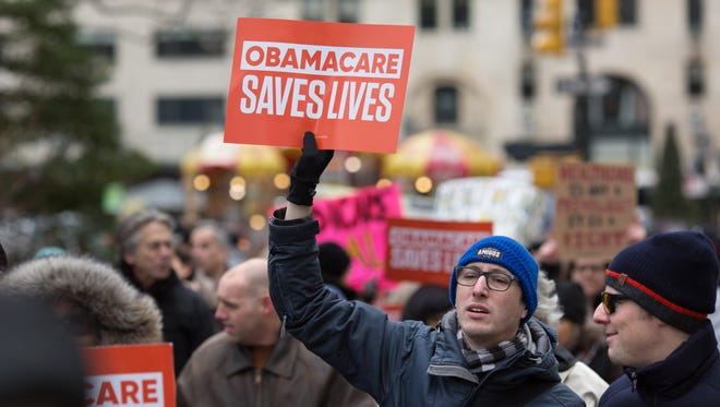 """Health care activists lift signage promoting the Affordable Care Act during a rally as part of the national """"March for Health"""" movement in front of Trump Tower on April 1, 2017 in New York City."""