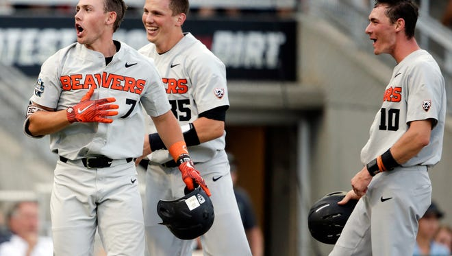 Oregon State's Tyler Malone (7) celebrates his three-run home run against Mississippi State in the third inning with Adley Rutschman (35) and Michael Gretler (10) in an NCAA College World Series baseball elimination game in Omaha, Neb., Saturday, June 23, 2018. (AP Photo/Nati Harnik)