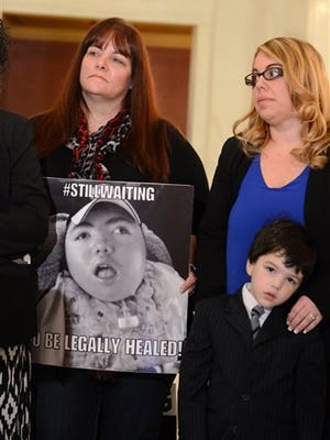 Diana Briggs, left, Jamie Messersmith and Cooper Salemme listen at a news conference in the Pennsylvania Capitol where parents of children suffering from debilitating seizures urged the state House of Representatives to pass medical marijuana legislation, Wednesday, April 13, 2016, in Harrisburg, Pa. Briggs, of Export, is holding a photo of her son Ryan, 15, who suffers daily seizures, and cannot walk or talk. Messersmith's nephew and Salemme's brother Jackson, 9, also suffers daily seizures.