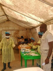 In this photo taken on Sunday, July 27, 2014, medical personnel work at the Doctors Without Borders facility in Kailahun, Sierra Leone where Dr. Sheik Humarr Khan died. He had been hospitalized in quarantine.