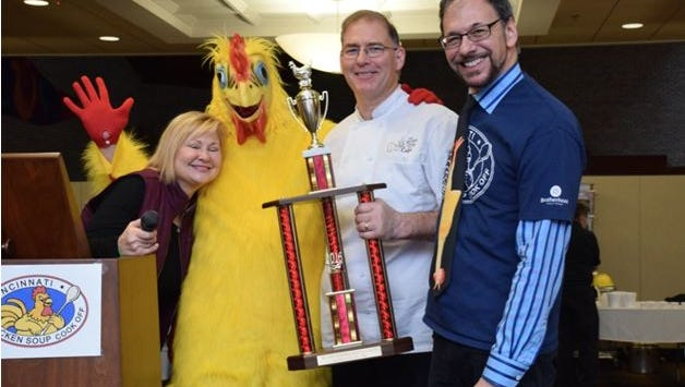 Shawn McCoy, of Brown Dog Cafe, holds his winning trophy from the 2016 Chicken Soup Cook-off, with organizer Jay Rissover and judge Janeen Coyle of WGGR
