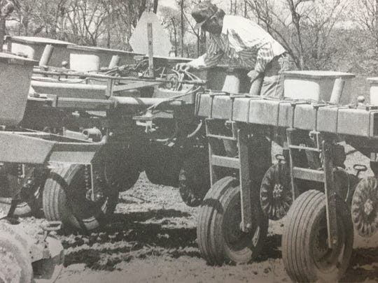 Joe Welden inspected the hydraulic hoses on a 12-row corn planter as he planted corn on 40 acres of property owned by his father-in-law in April 1997.