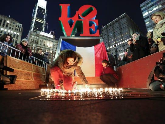 Cloe Tinchant lights candles in LOVE Park, Saturday,