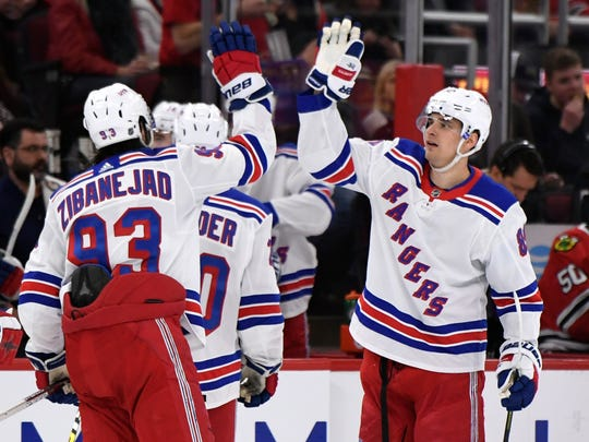New York Rangers' Pavel Buchnevich (89) of Russia, celebrates with teammate Mika Zibanejad (93) of Sweden, during the third period of an NHL hockey game against the Chicago Blackhawks Wednesday, Feb. 19, 2020, in Chicago. New York won 6-3. (AP Photo/Paul Beaty)