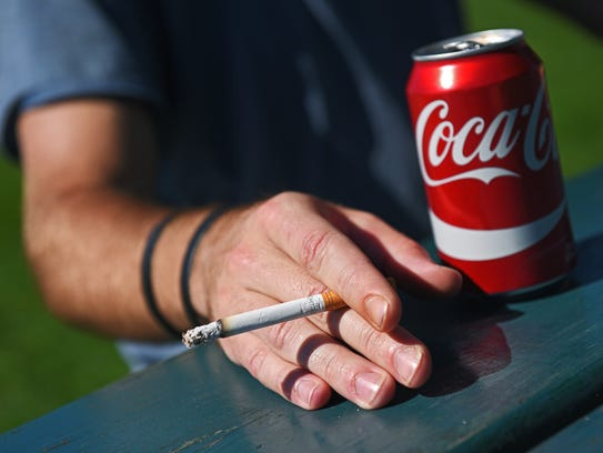 Daniel Eastman, 30, of Sioux Falls, smokes a cigarette