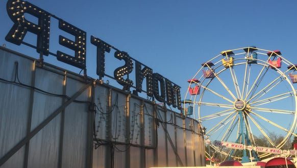 The setting sun lights up the Ferris wheel, while a