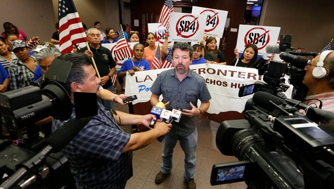 "Fernando Garcia, executive director of the Border Network for Human Rights in El Paso, addresses the media shortly after the County Commissioners Court voted to move forward with legal action against the state regarding the so-called ""show me your papers"" bill set to go into effect Sept. 1."