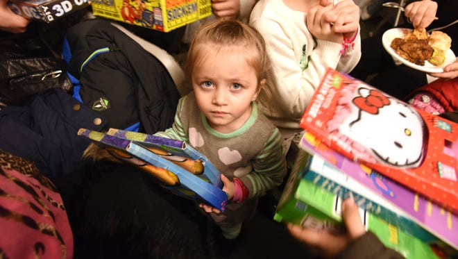 Three-year-old Rimas Ismail with her gifts from a gathering in Paterson on Thursday to welcome 15 Syrian refugee families that recently arrived in Passaic County.