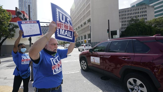 """Postal worker Gabriel Rial, foreground, chants as he demonstrates during a """"National Day of Action to Save the """"Peoples"""" Post Office!"""" outside the Flagler Station post office, Tuesday, Aug. 25, 2020, in Miami. The pandemic has pushed the Postal Service into a central role in the 2020 elections, with tens of millions of people expected to vote by mail rather than in-person. At the same time, Trump has acknowledged he is withholding emergency aid from the service to make it harder to process mail-in ballots, as his election campaign legally challenges mail voting procedures in key states."""