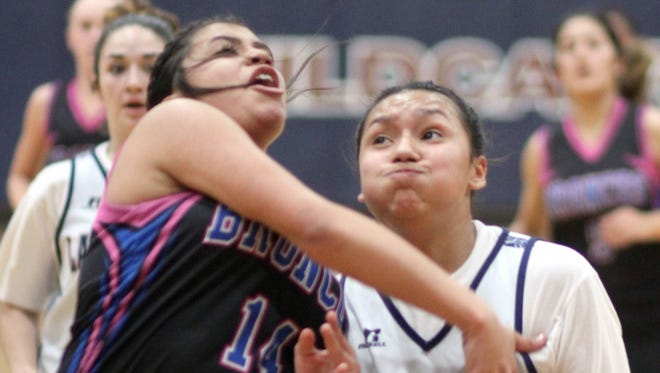 Lady Cat Harmanie Dominguez (with ball) takes a hard drive to the basket for two of her game-high 13 points in a 31-16 Lady Cat victory over the visiting La Plata Broncos on Tuesday, Jan. 16.