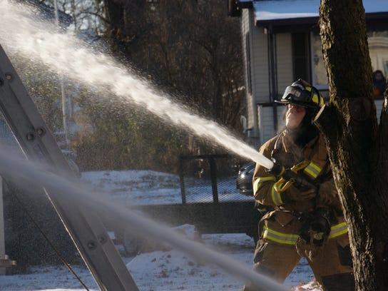 Water is directed on a frigid morning at flames from