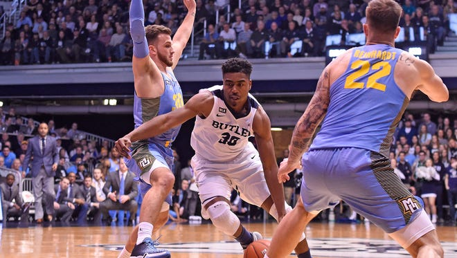 Butler Bulldogs forward Kelan Martin (30) dribbles the ball between Marquette Golden Eagles guard Andrew Rowsey (30) and guard Katin Reinhardt (22) in the second half at Hinkle Fieldhouse.