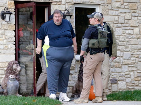 Todd Brunner is seen exiting his home after being arrested