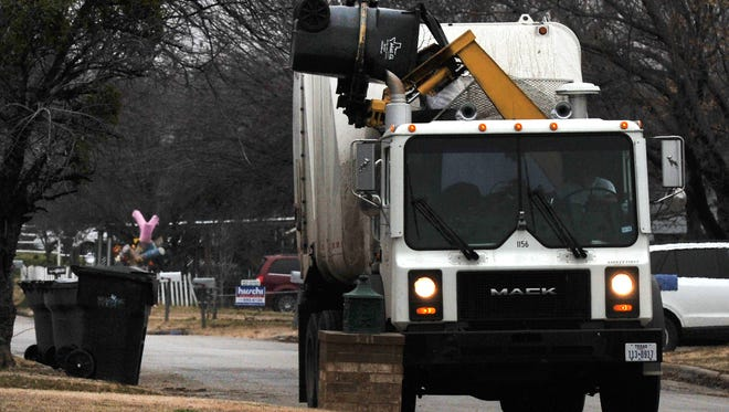 CHRISTOPHER WALKER/TIMES RECORD NEWS     A Wichita Falls sanitation truck picks-up a roll-off trash can..