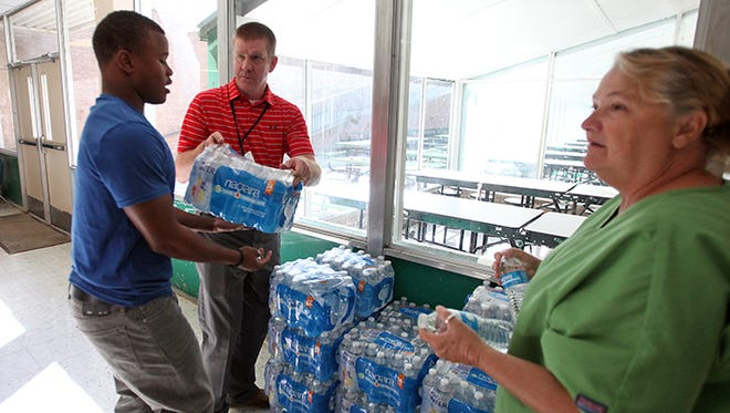 Vicksburg assistant principal Jason Bennett, center, passes out water to students Wednesday, Aug. 26, 2015, at VHS after a boil water notice was issued for the city water supply.