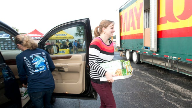 """Volunteer Lauren Meadors, helps unload a food donation dropped-off a Cordova Mall for the """"Fill the Mayflower"""" during last year's event. Manna Food Pantries will be collecting food and monetary donations at the Ninth Avenue on Nov. 21 and 22"""