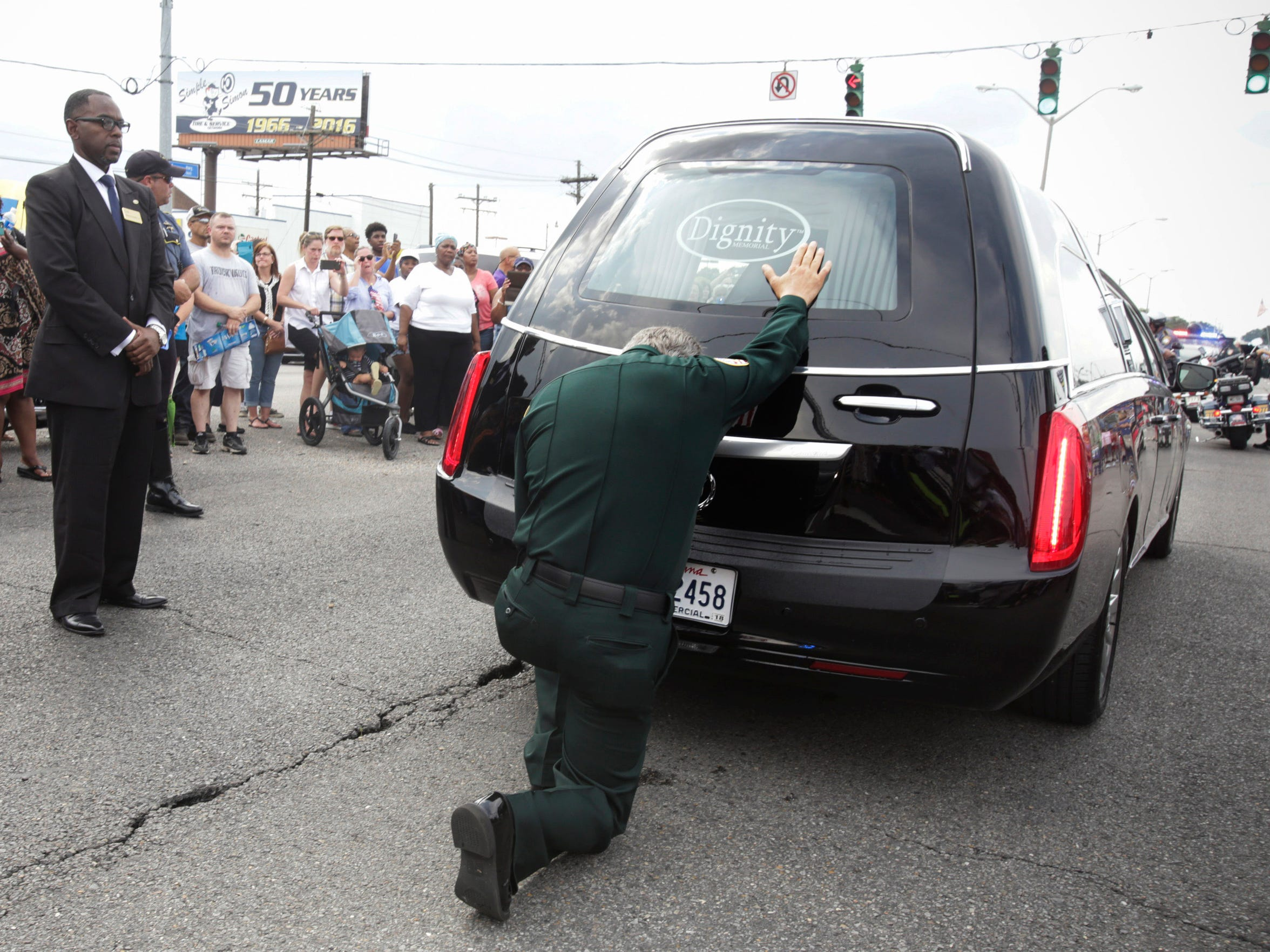 East Baton Rouge Sheriff Sid Gautreaux prays at the hearse carrying his deputy Brad Garafola- one of three Baton Rouge law enforcement officers killed in a July 17 shootout- near the site of the shooting in Baton Rouge July 23.