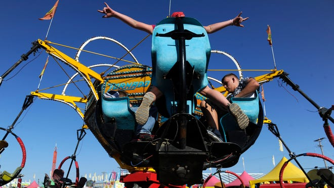 Abby Lowe, 11, spreads her arms as she rides the Tornado with Bryan Skiles, 15, (right) and her brother Matthew, 15 Thursday at the West Texas Fair & Rodeo. Thursday was Sneak-a-Peek night. The fair runs through Sept. 16.