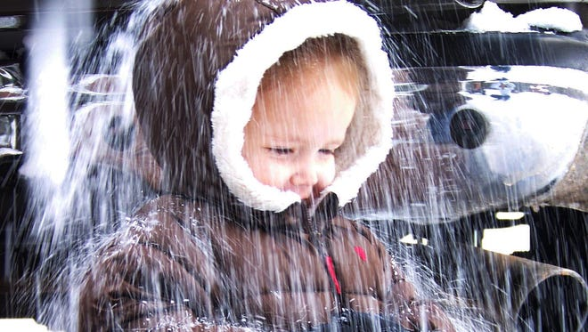 A bundled-up child enjoying the snow that was falling in Pine in 2013.