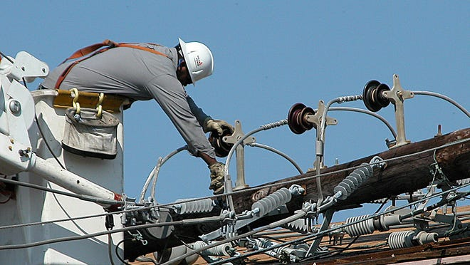 Gulf Power utility workers restore power lines after Hurricane Ivan in 2004.