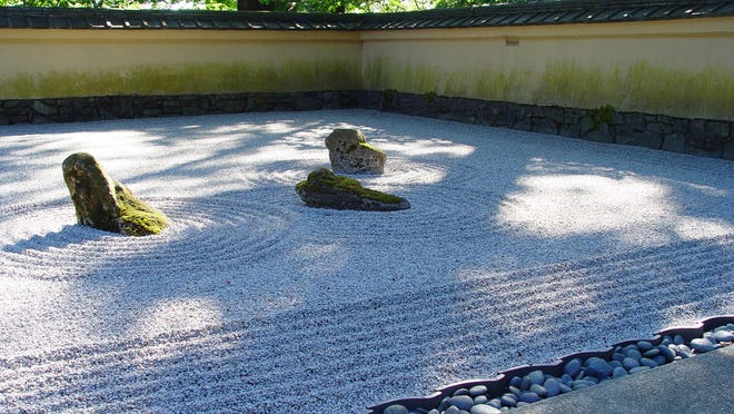 """Pea gravel is raked into ripples around these """"reclining"""" stones which Japanese garden masters likened to recumbant animals."""