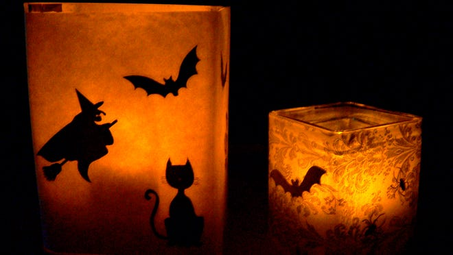 In this Oct. 13, 2014 photo, you can lighten up Halloween night with do-it-yourself luminaries. Attach black stickers to vellum or the waxy side of freezer paper and wrap around a clear glass vase, adhering with double-sided tape. Insert battery-operated votives and enjoy the trembling glow. (AP Photo, Jennifer Forker)