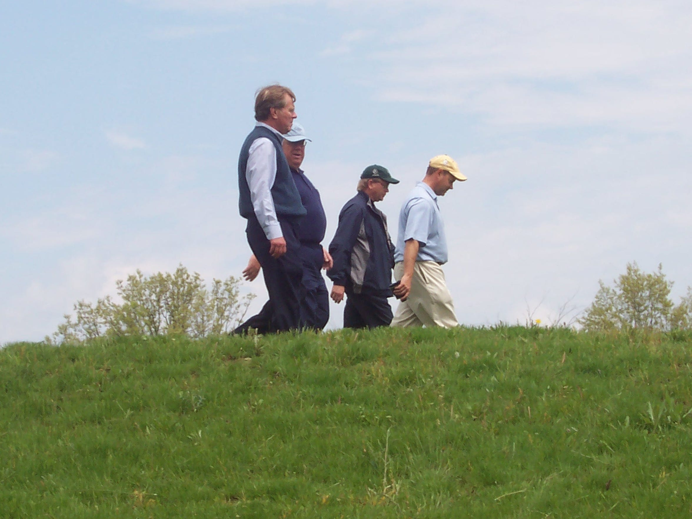 Mike Davis (in yellow hat), now the executive director of the USGA, and Bob Lang (foreground) walk Erin Hills during a scouting visit in 2006.