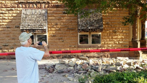 FILE - In this Saturday, Sept. 3, 2016 file photo, Steve Gibson, of Pawnee, takes photos of damage to a building in downtown Pawnee, Okla., following a 5.6 magnitude earthquake. An Oklahoma-based Native American tribe, the Pawnee Nation, filed a lawsuit in its own tribal court system accusing several oil companies in the state's largest earthquake that caused extensive damage to some near-century-old tribal buildings.