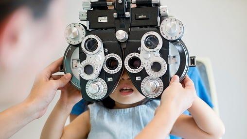 Girl having her eyes tested.