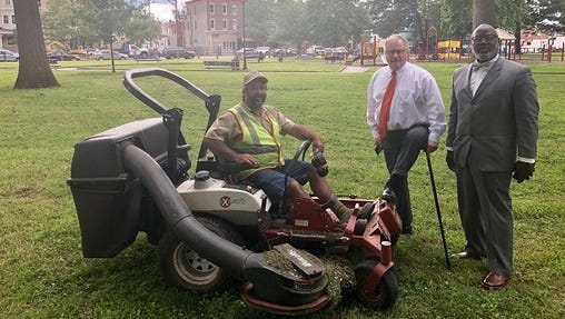 Scott Wagner in Malcolm X Park post-cleanup, accompanied by a contractor, supporter and lawnmower.