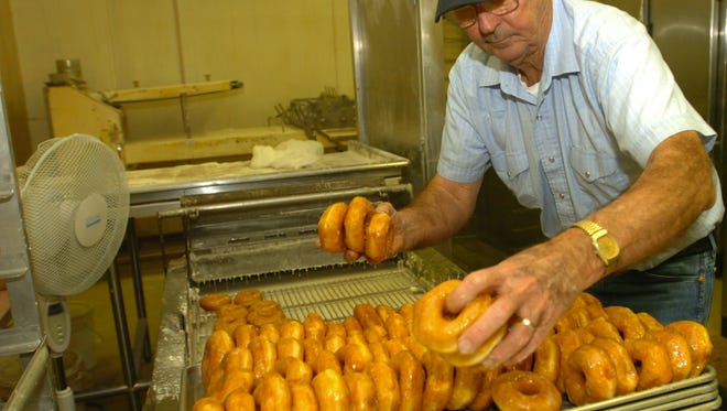 Roy Burr Sr. lines fresh donuts on a tray for sale in 2007. The longtime Harlow's Donuts and Bakery owner passed away this week.