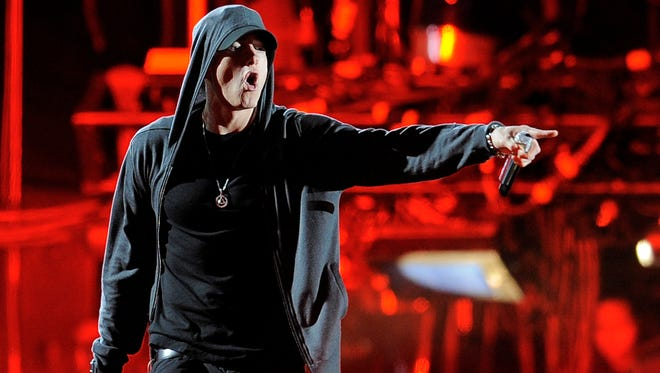 This April 15, 2012, photo shows Eminem performing at the 2012 Coachella Valley Music and Arts Festival in Indio, Calif. Eminem and Outkast will headline this year's Lollapalooza music festival on Aug. 1-3, 2014, in Chicago.