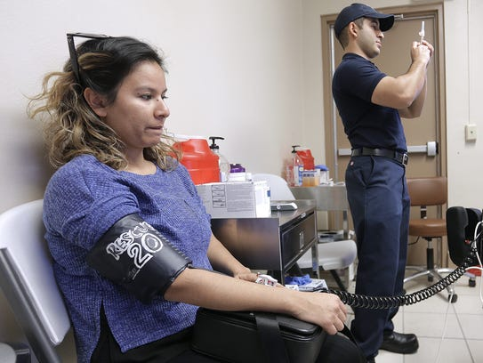 Lucia Aguirre has her blood pressure taken while El