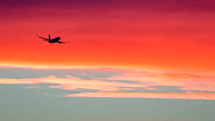 A jetliner goes off into the wild red yonder as it climbs out of Sky Harbor International Airport in this photograph taken by Archie Tucker from the Desert Botanical Garden.