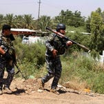 Iraqi federal policemen patrol in the town of Taji, about 12 miles north of Baghdad, Iraq, Thursday. The Islamic State of Iraq and the Levant (ISIL) took over the country's second largest city 10 days ago. U.S. Secretary of State John Kerry warned Mideast nations on Wednesday against taking new military action in Iraq that might heighten already-tense sectarian divisions, as reports surfaced that Syria launched airstrikes across the border and Iran has been flying surveillance drones over the neighboring country.