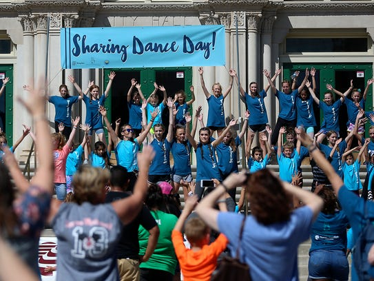 Dancers perform before a large crowd of people on the