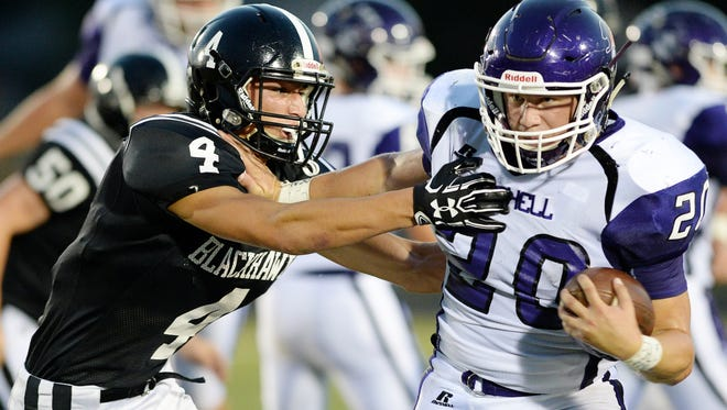 Mitchell's Ben Robinson (20) carries the ball in Friday's game at North Buncombe.