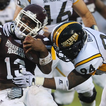 Southern Miss' Dylan Bradley (94) wraps up Mississippi State's Cedric Jiles (13) during their season opener in Starkville.