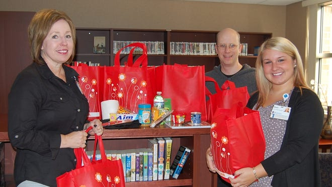 From left: Michelle Ries, Agnesian HealthCare Foundation events coordinator; and Megan Feilbach, Samaritan Health Clinic office support specialist accepted donations from four area churches to aid Samaritan patients. Brian Hastings, Memorial Baptist Church pastor, in back, presented the donation.