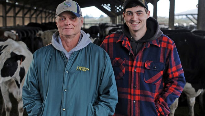 This photo taken March 2, 2018, shows Andrew, left, and Charlie Dykstra stand with their cattle at their farm north of Burlington, Wash.   Conventional dairy farms have been struggling for years. Until recently, Dykstra said it seemed organic dairy farms were somewhat shielded from the volatility of the conventional market. Now, organic dairies are struggling alongside conventional dairies, further adding to the impact on the local agriculture economy.