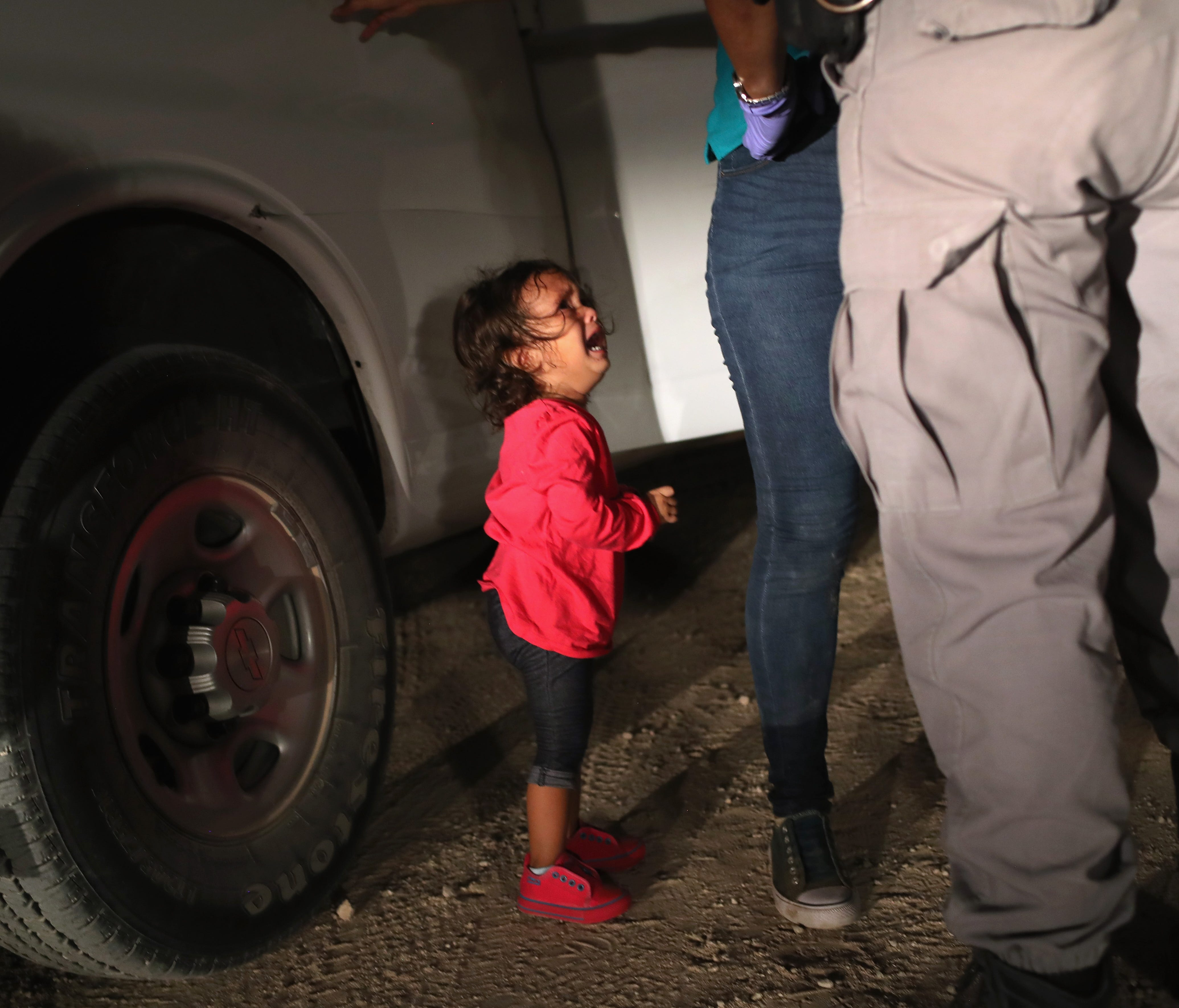 A two-year-old Honduran asylum seeker cries as her mother is searched and detained near the U.S.-Mexico border on June 12, 2018 in McAllen, Texas. The asylum seekers had rafted across the Rio Grande from Mexico and were detained by U.S. Border Patrol
