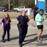 A Waveland, Miss.police officer (2nd from left) joins in a line dance at a Mardi Gras parade.