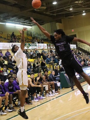 Oklahoma Baptist University's Jarius Hicklen successfully connects on a 3-point jumper from the corner over Ouachita Baptist's leaping Kendarious Smith (21) Thursday night at the Noble Complex.     PHOTO BY BRIAN JOHNSON