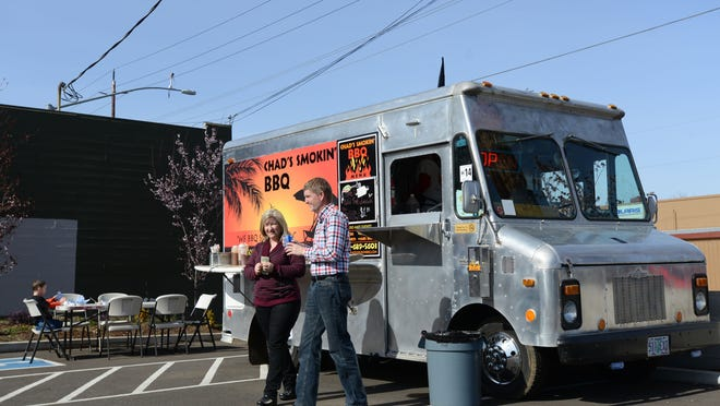 Tiina and Mike Downer of Keizer order from Chad's Smokin' BBQ during the opening of Salem's first food truck pod on Sunday, March 1, along Broadway NE in Salem.