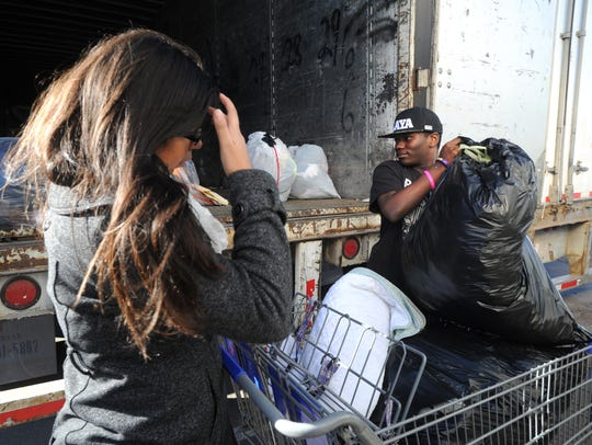 Alexandra Montez, left, and Jaquan Norman load bags