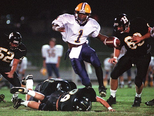 Smyrna quarterback Luke Powell leaps over Hendersonville  defender Tommy Ellis as he is pursued by Scott Medsker (left) and James Beasley (right) during a 1997 game.